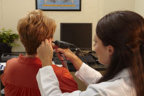 Female hearing professional taking a hearing screening of patient